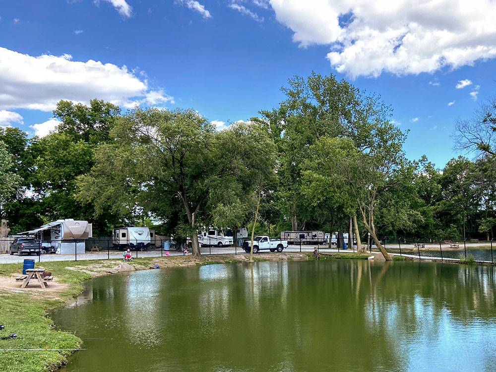 RVs parked at sites and man fishing at the lake at INDY LAKES RV CAMPGROUND