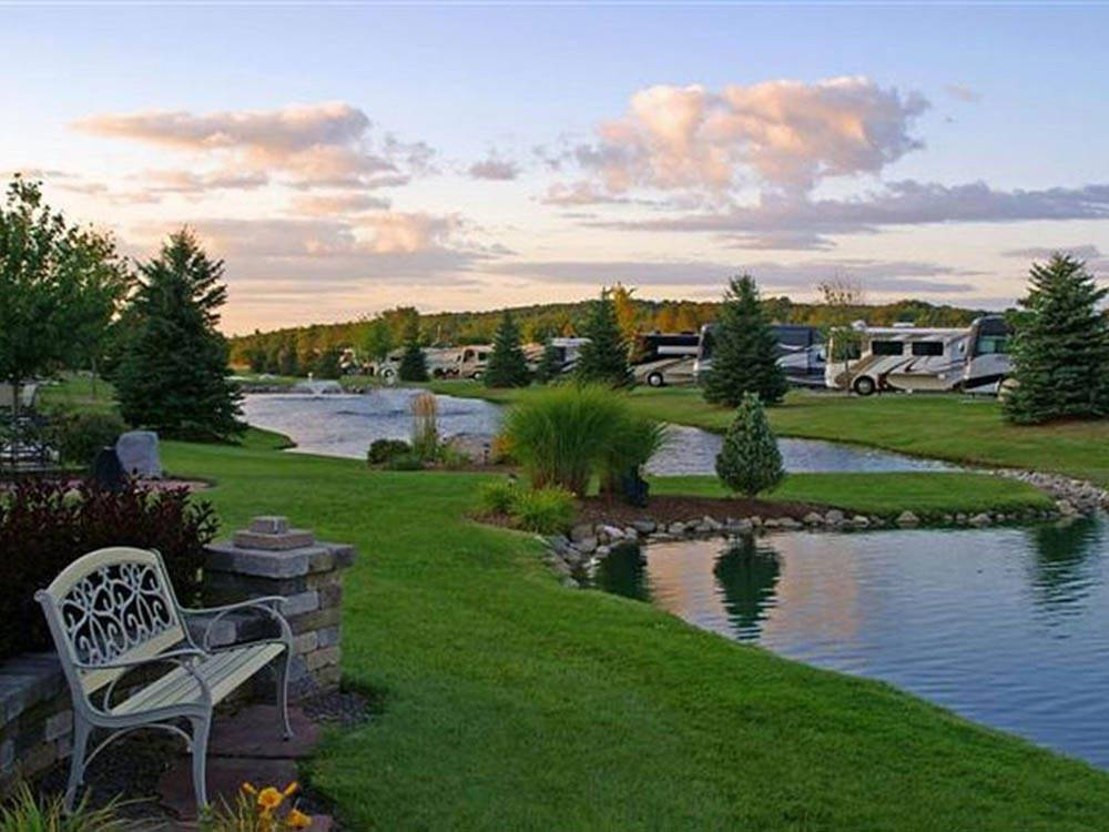 RVs parked near pretty lake and green grass at TRAVERSE BAY RV RESORT