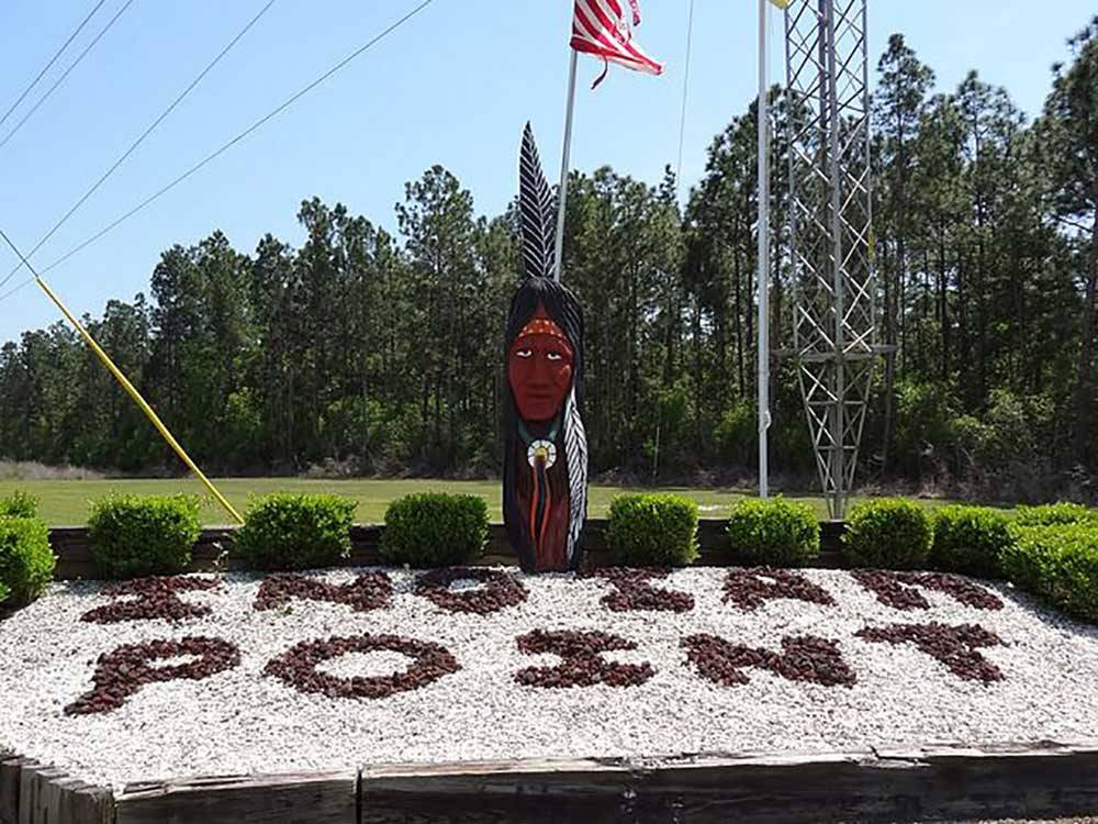 Indian statue next to rock sign at entrance at INDIAN POINT RV RESORT