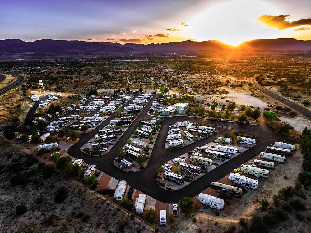 Aerial view over RV campground and mountains at sunset at DISTANT DRUMS RV RESORT