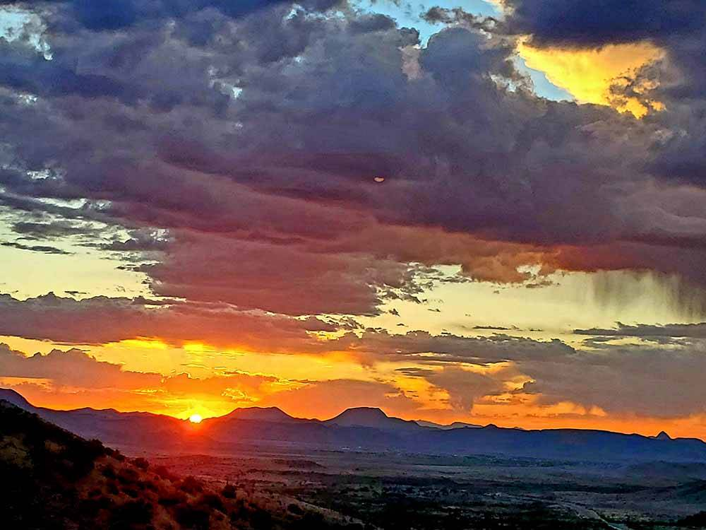 Vast open land with green shrubs abound and white trailer parked on dirt path at LA VISTA RV PARK