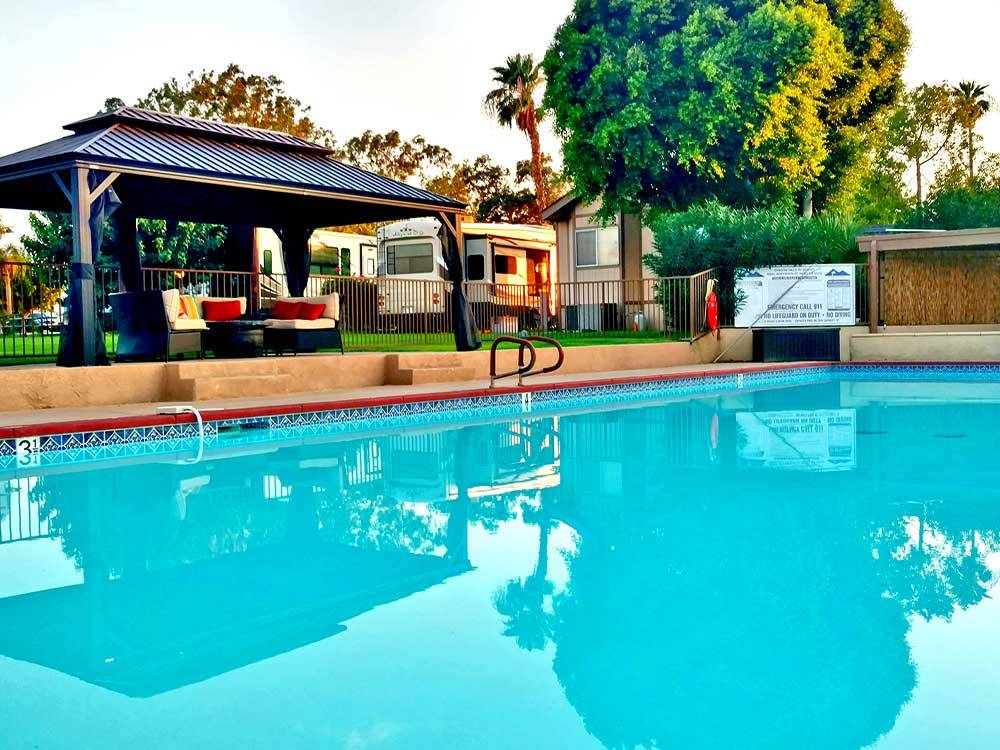 Swimming pool with covered seating area at SHADOW HILLS RV RESORT