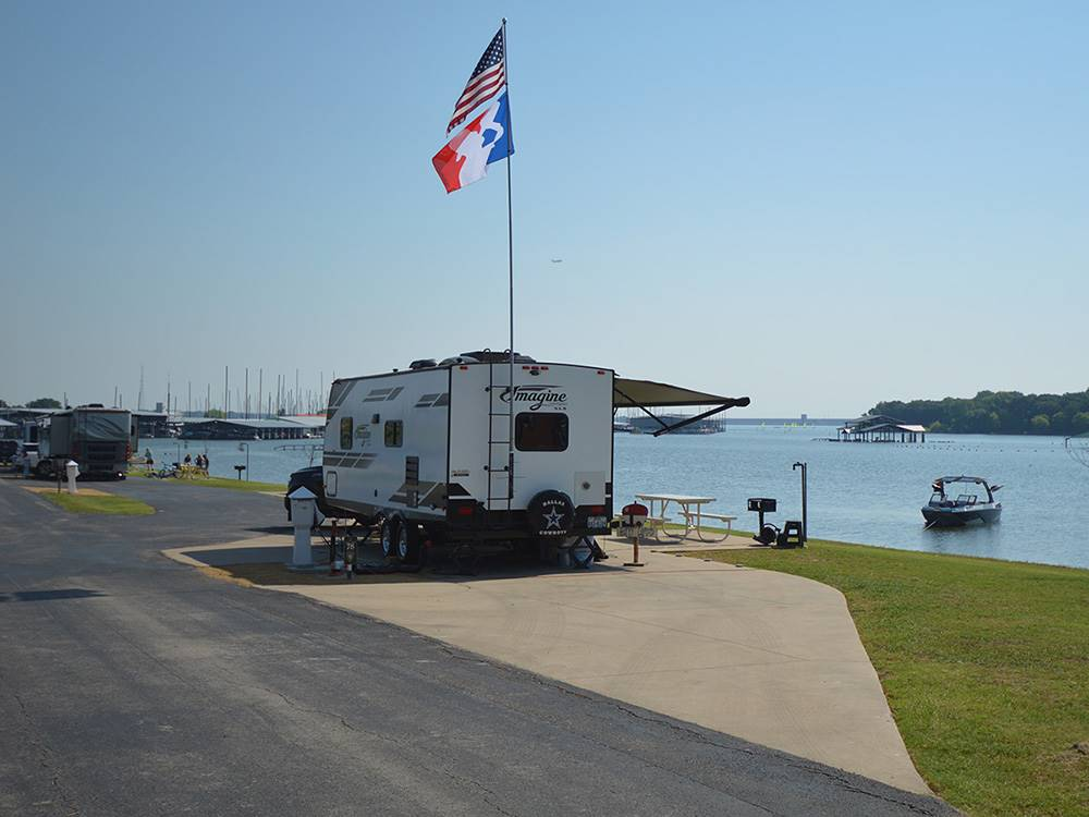 RV with slideouts at a waterfront site at THE VINEYARDS CAMPGROUND  CABINS