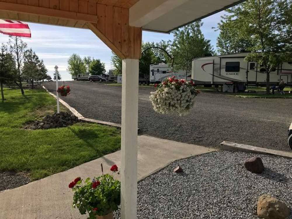 View of RVs in sites off a gravel road at BEAR DEN RV PARK