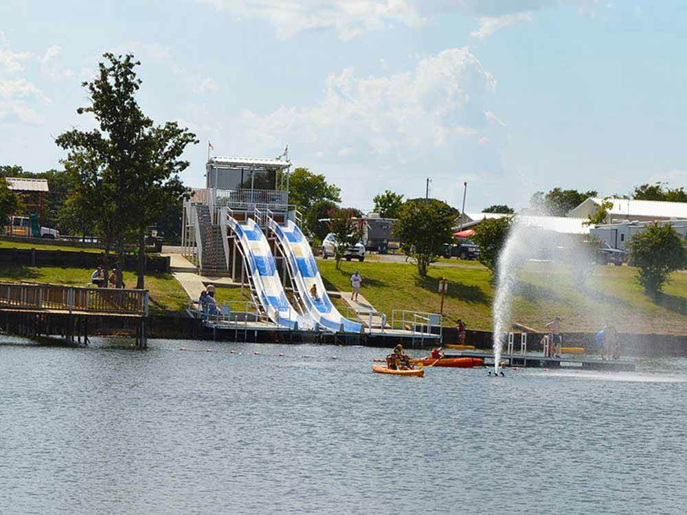 Double water slide pouring into lake at HIDDEN LAKE RV RESORT