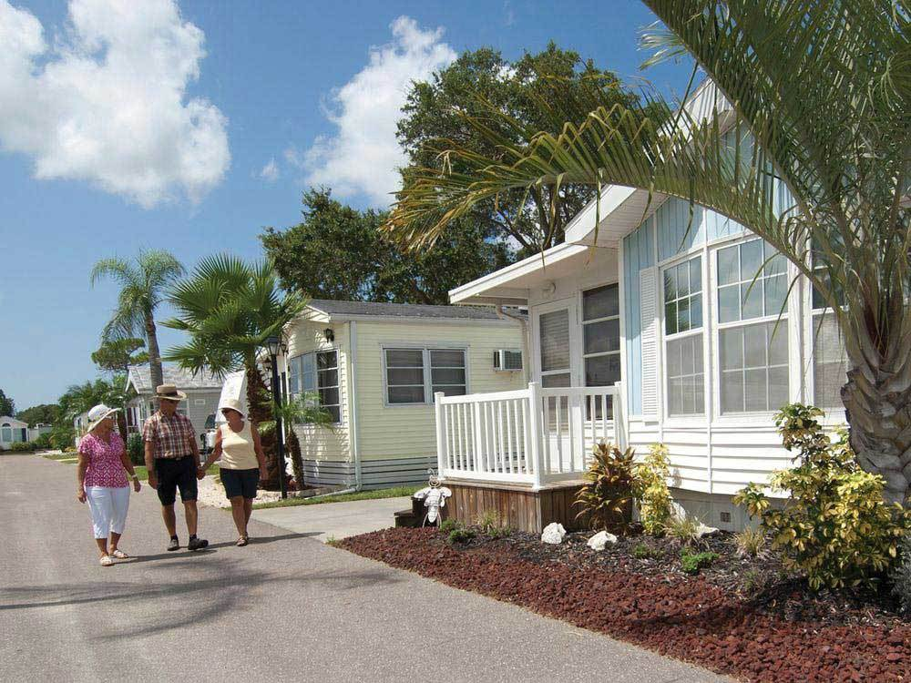 Campers walking beside mobile homes at RAINBOW VILLAGE OF LARGO RV RESORT