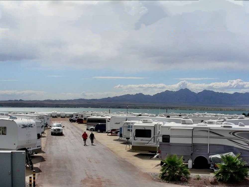 A row of RVs parked in sites with mountains in the background at CAMPBELL COVE RV RESORT