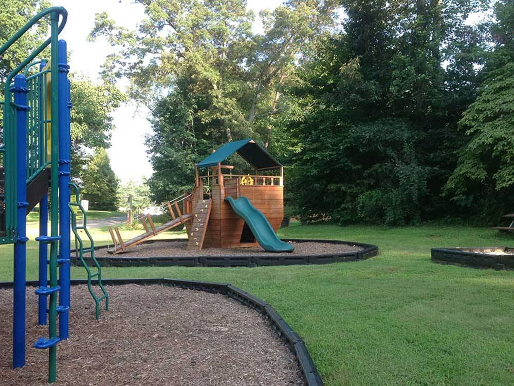 Wooden ship structure with a slide and climbing wall at the Playground at MADISON VINES RV RESORT  COTTAGES