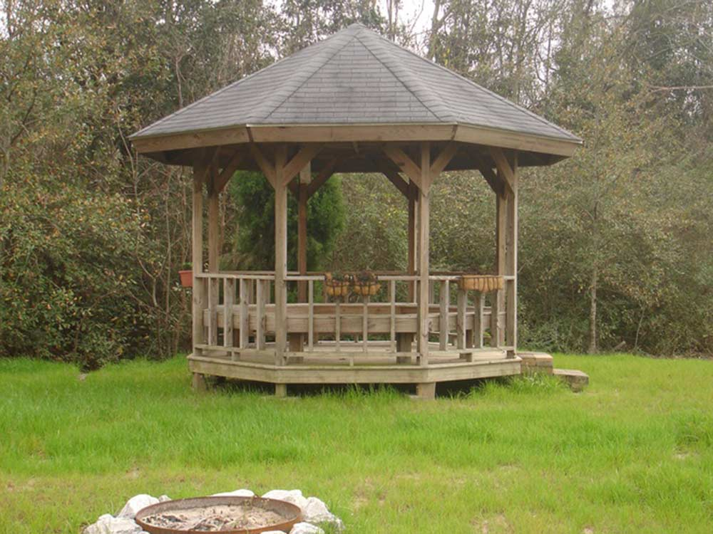 Wooden gazebo on grassy lawn with trees in background at OAKLAWN RV PARK