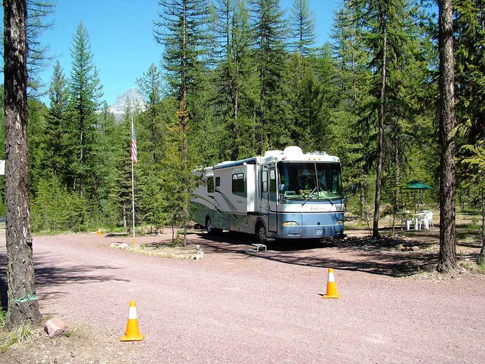 Big rig in site with trees off gravel road at GLACIER HAVEN RV  CAMPGROUND
