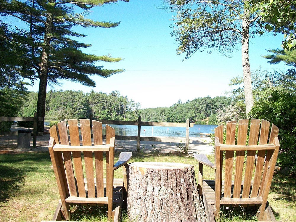 View of lake from Adirondack chairs at PINEWOOD LODGE CAMPGROUND
