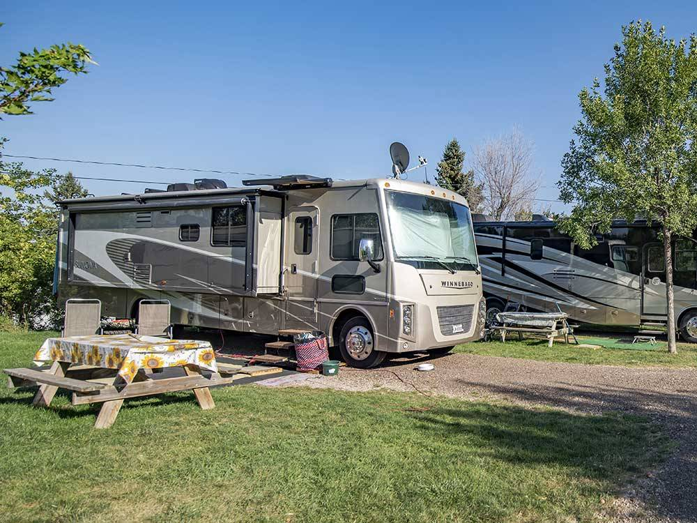Large RVs parked in gravel sites with picnic tables at CHRIS CAMP  RV PARK