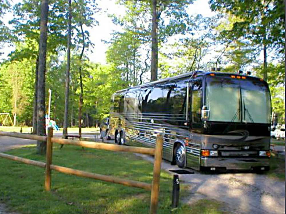 Class A motorhome on gravel site with picnic table surrounded by tall trees at ELIZABETHTOWN CROSSROADS CAMPGROUND