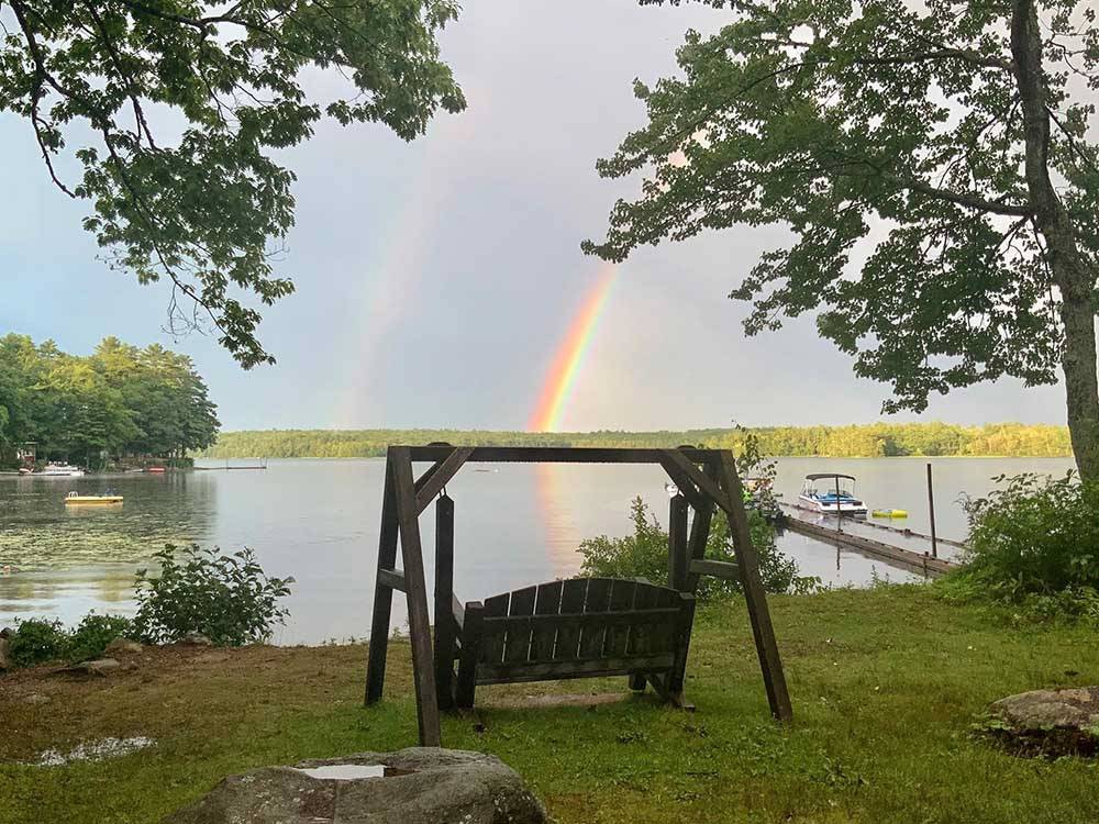 Sunset reflected on the lake through trees at LAKE PEMAQUID CAMPGROUND