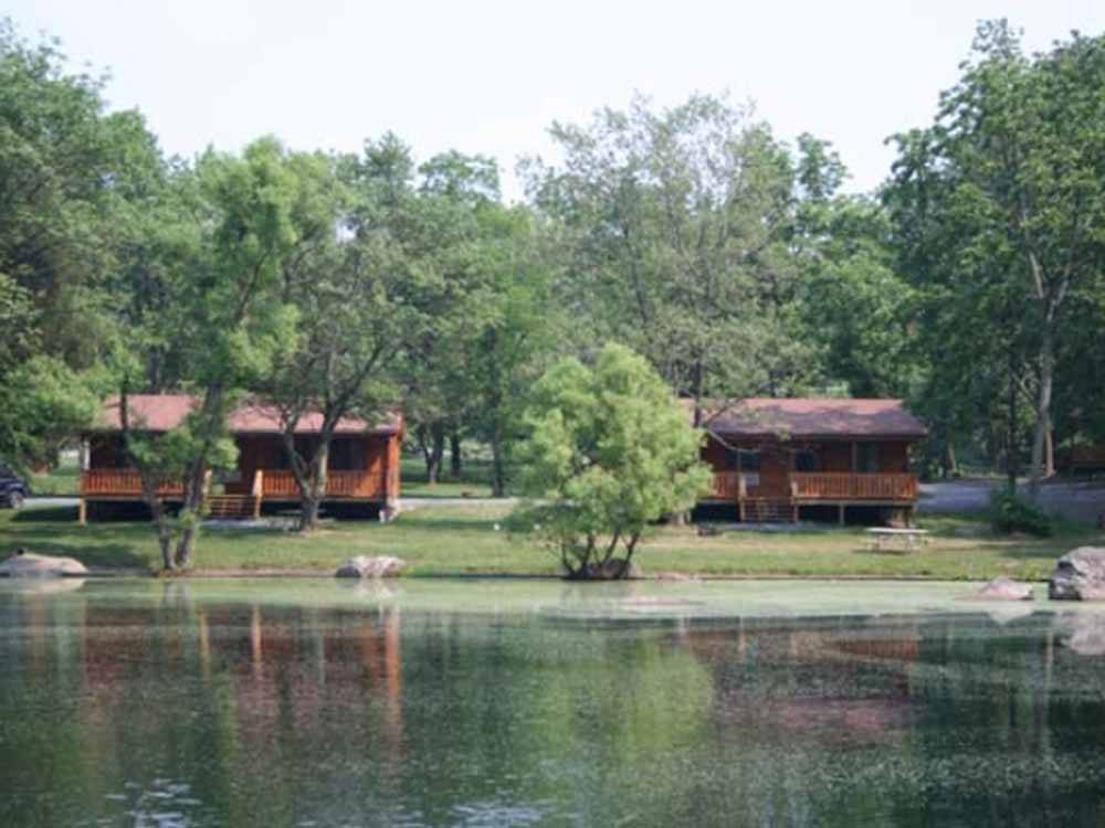 A couple of camping cabins by the water at DRUMMER BOY CAMPING RESORT