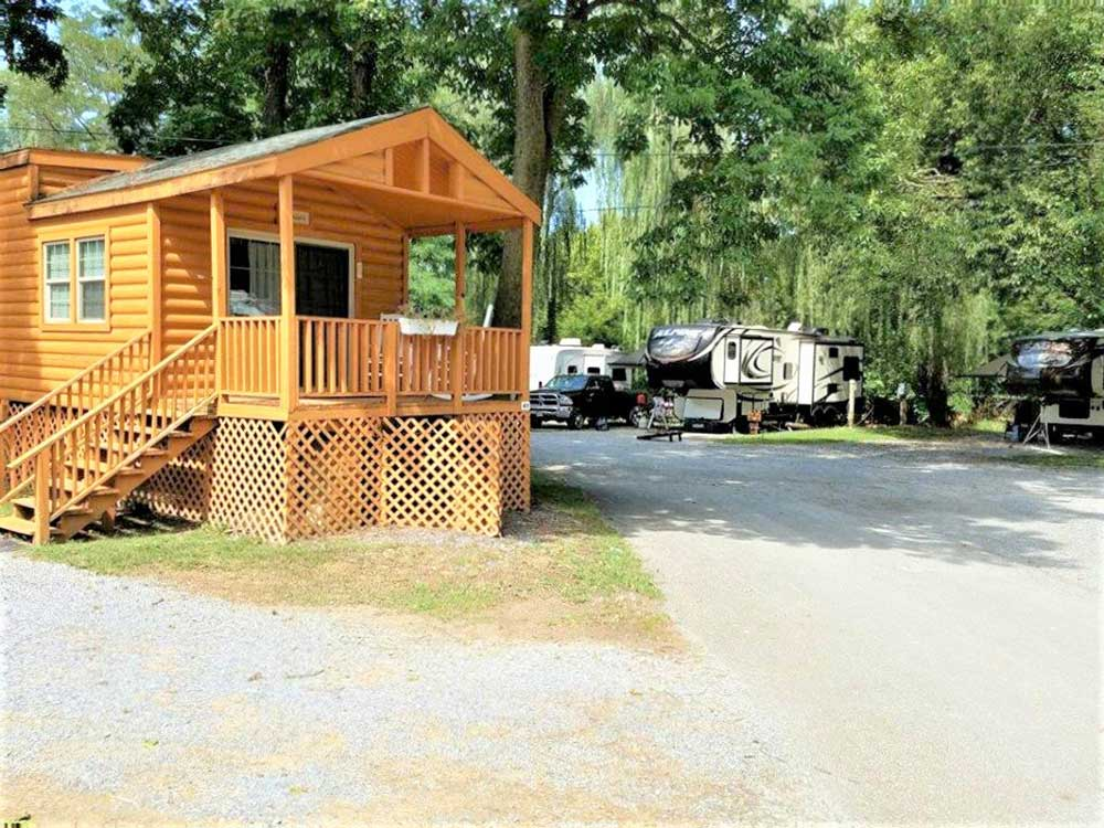 Cabin with porch RVs parked under shade trees in back at MILL BRIDGE VILLAGE AND CAMPRESORT