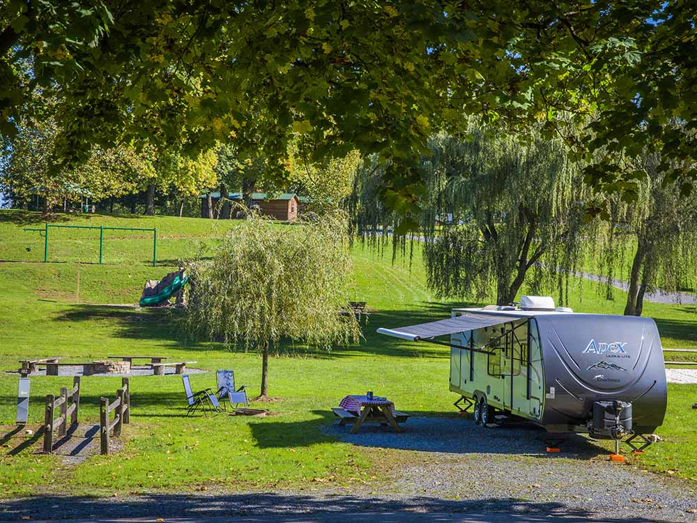 A gravel RV site with a picnic table at HERSHEYPARK CAMPING RESORT