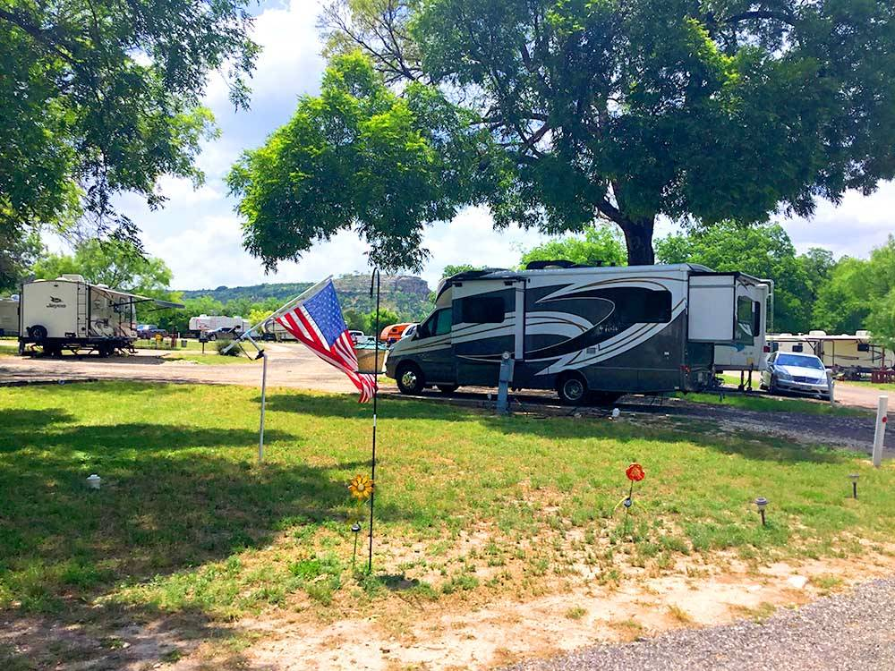 A Class C motorhome parked under a tree at 1083 RV PARK