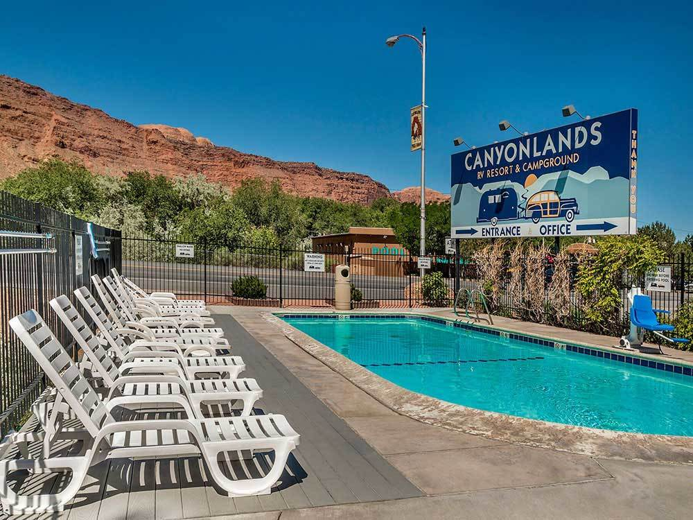 Swimming pool with outdoor seating at CANYONLANDS CAMPGROUND