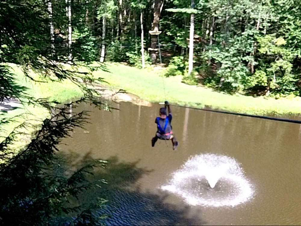Man zip lining over a fountain in the lake  at WILD ACRES RV RESORT  CAMPGROUND