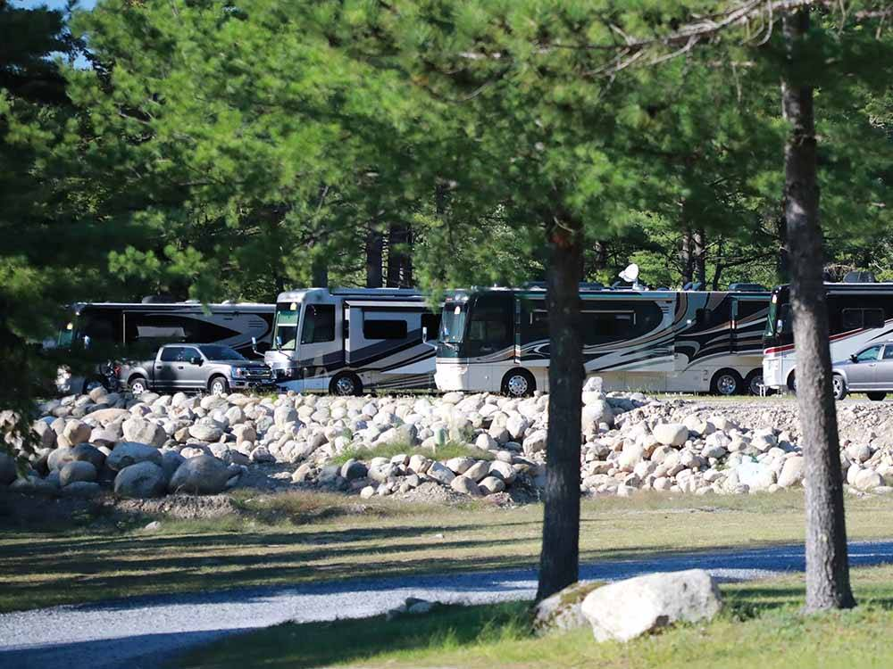 A row of Class A motorhomes parked along rocks at LAKE GEORGE RIVERVIEW CAMPGROUND