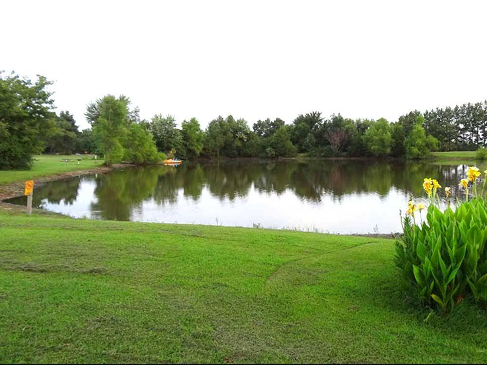 View of pond surrounded by grass flowers and trees at FORT SMITH-ALMA RV PARK