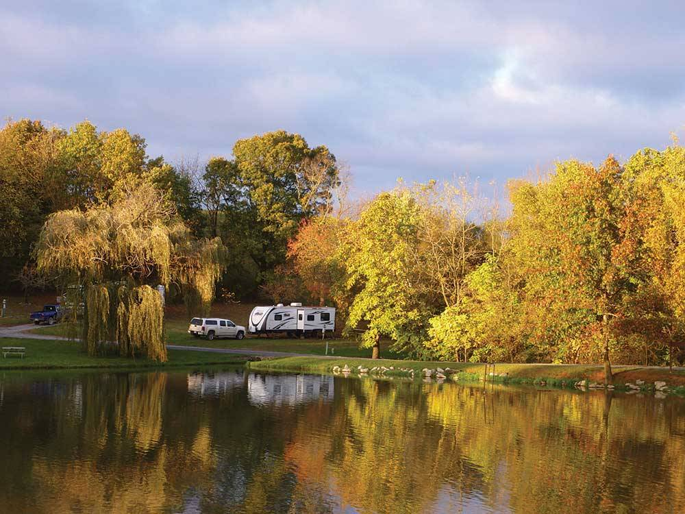 RV parked next to lake with fall foliage at WALNUT HILLS CAMPGROUND AND RV PARK
