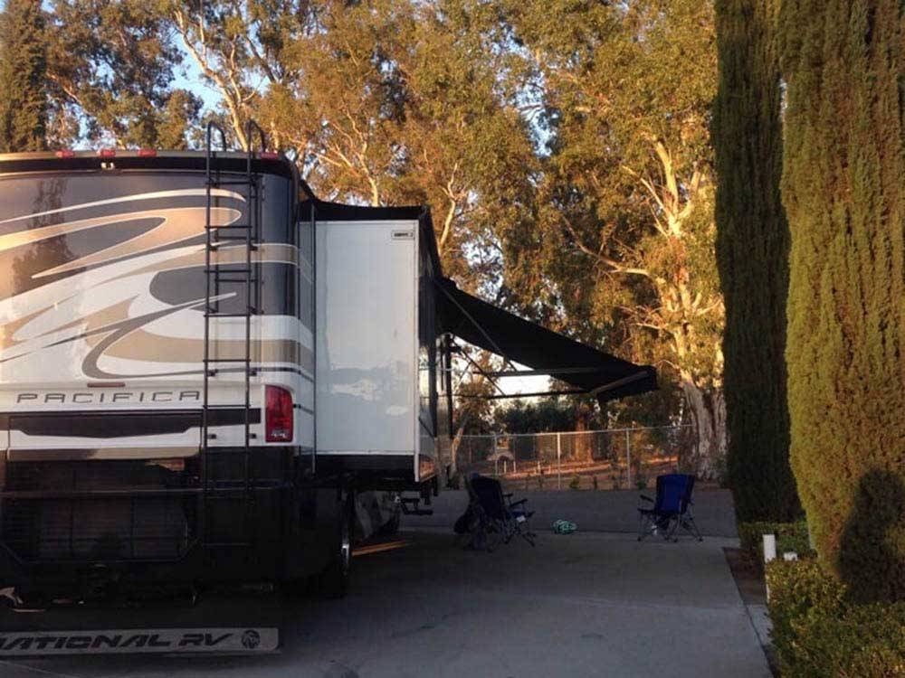 Large brown tan and white travel trailer with awning at SANTA NELLA RV PARK