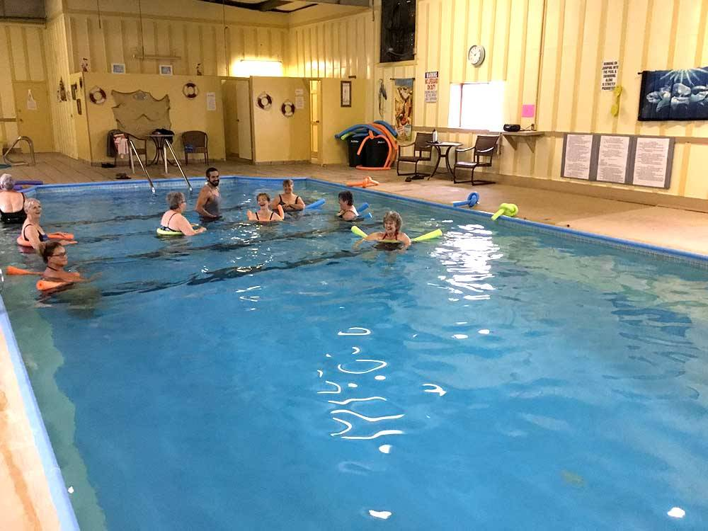 A group of adults swimming in an indoor pool at ALAMO REC-VEH PARKMHP