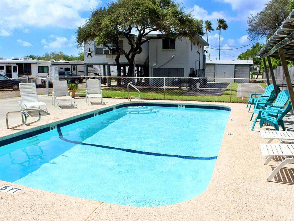 Pool with outdoor seating at PADRE PALMS RV PARK