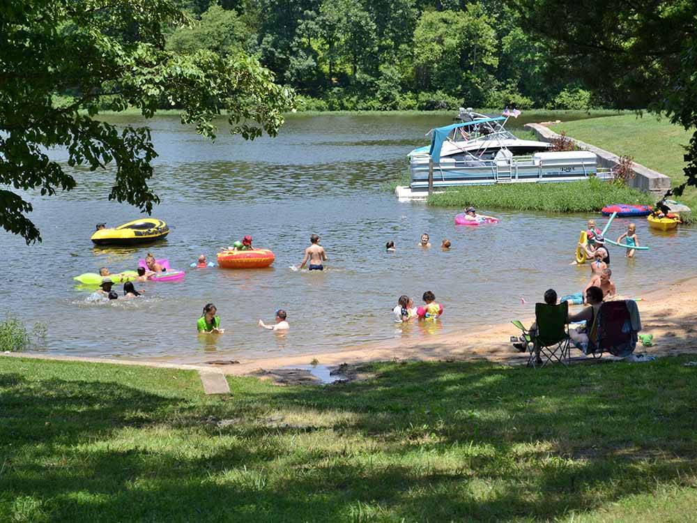 Boats docked on water with trees and grass at CHRISTOPHER RUN CAMPGROUND
