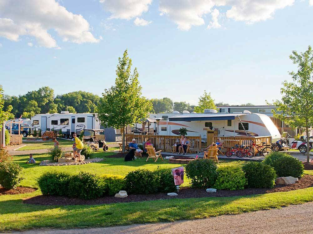 Trailers camping with people outside on sunny day at OCONNELLS YOGI BEAR PARK