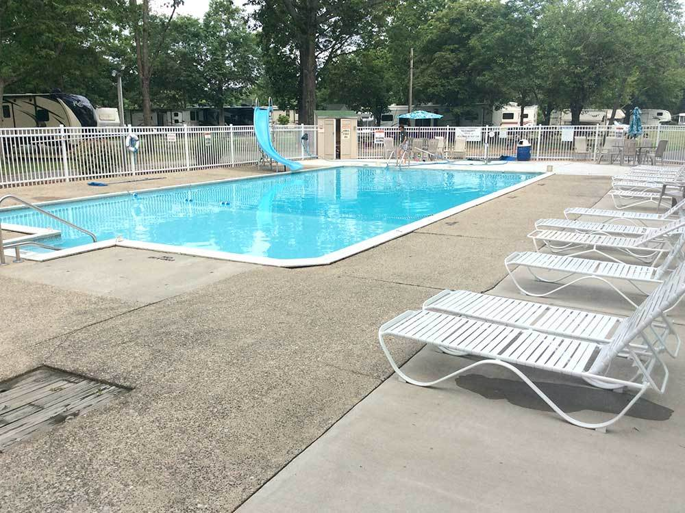 Fenced pool area with chaise lounges at POMONA RV PARK
