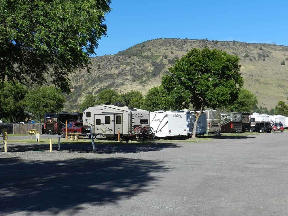 RVs parked in gravel sites with grass at OREGON MOTEL 8  RV PARK