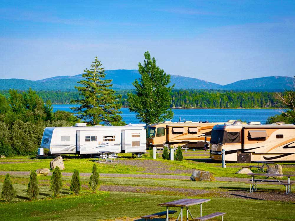 Large trailers and RVs parked alongside large lake at NARROWS TOO CAMPING RESORT