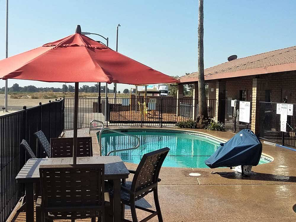 Table and chairs with an umbrella at poolside at SUN  FUN RV PARK