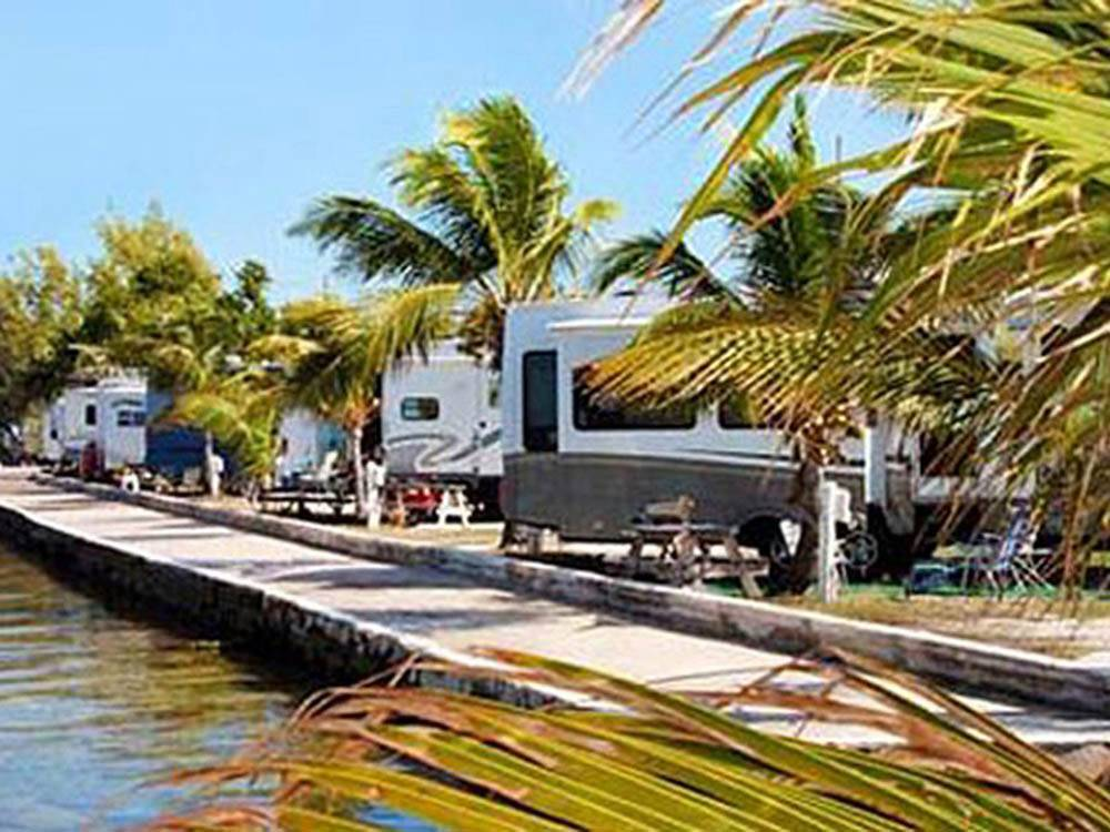 Multiple trailers parked alongside dock on the water at JOLLY ROGER RV RESORT