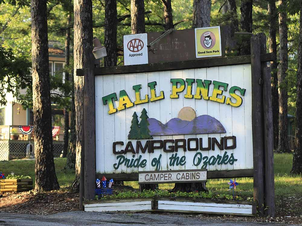 Trailer and pickup in a gravel site with trees at TALL PINES CAMPGROUND