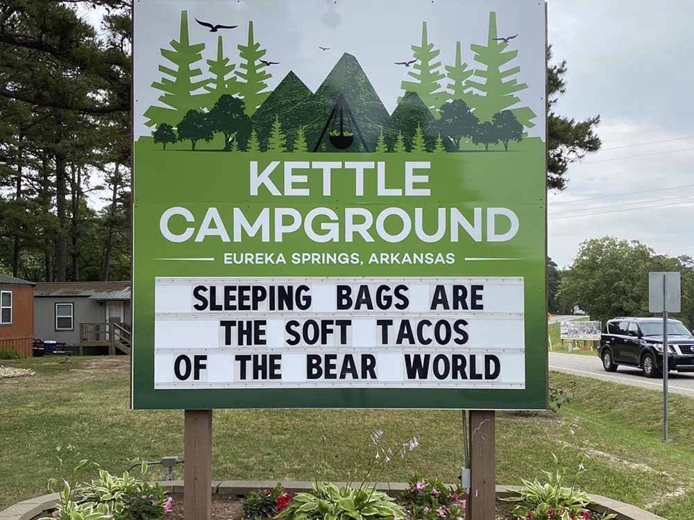 Large RV in wooded site near a wood carved bear holding a park welcome sign at KETTLE CAMPGROUND CABINS  RV PARK