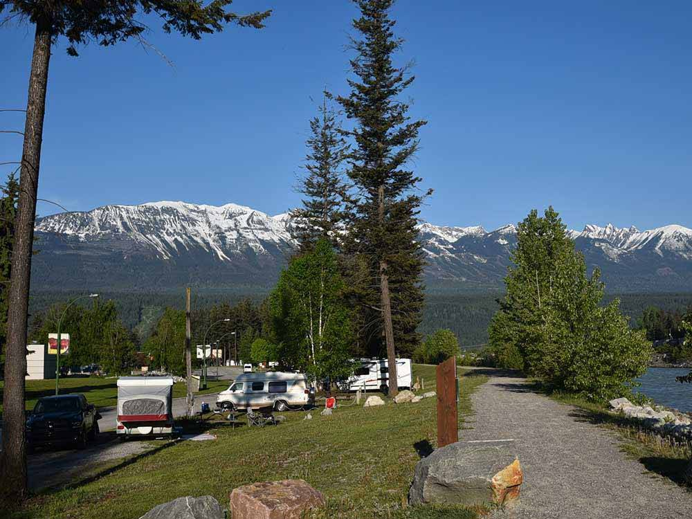 RV parked on grass site with tall trees River and mountains in background at GOLDEN MUNICIPAL CAMPGROUND