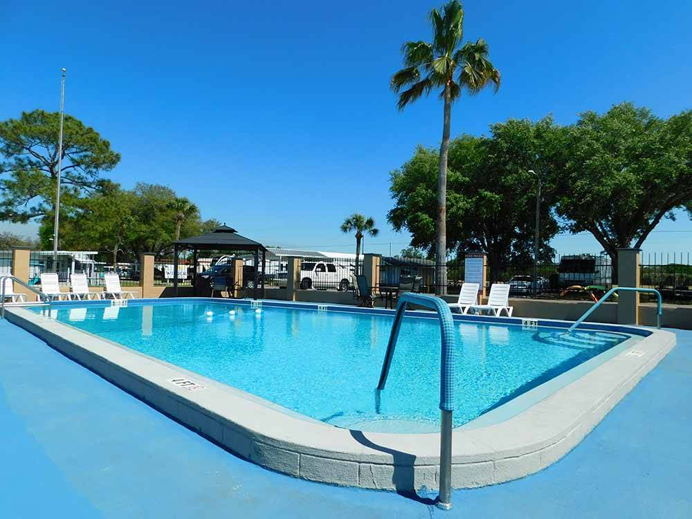 The pool area with chairs at PALM VIEW GARDENS RV RESORT