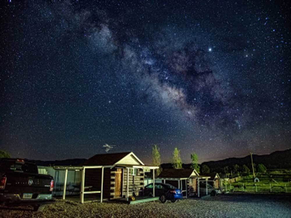 A row of cabins at night with visible Milky Way at ANCIENT CEDARS MESA VERDE RV PARK