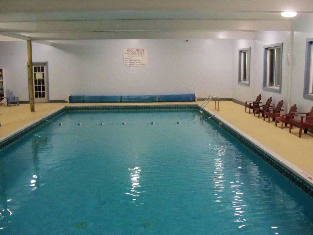 Indoor pool with chairs on the deck at BEECH HILL CAMPGROUND  CABINS