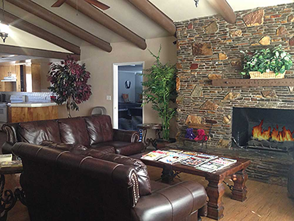 Interior of lodge with seating by the fireplace at ORCHARD RANCH RV RESORT