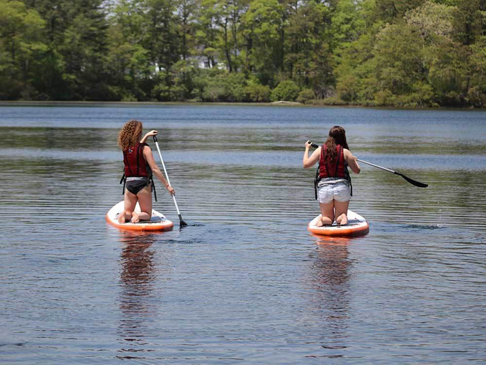 Girls paddle boarding at SANDY POND CAMPGROUND