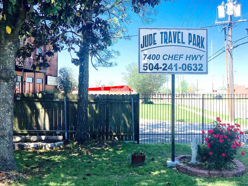 Entrance sign next to a flower planter at JUDE TRAVEL PARK OF NEW ORLEANS