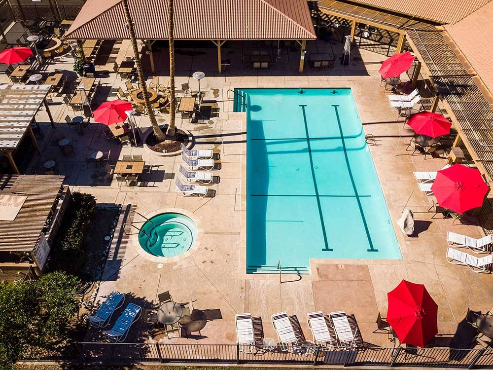 Aerial view over pool and spa with red umbrellas at RIO BEND RV  GOLF RESORT