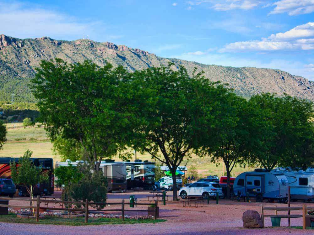 RVs parked in gravel sites under trees at ROYAL VIEW RV PARK