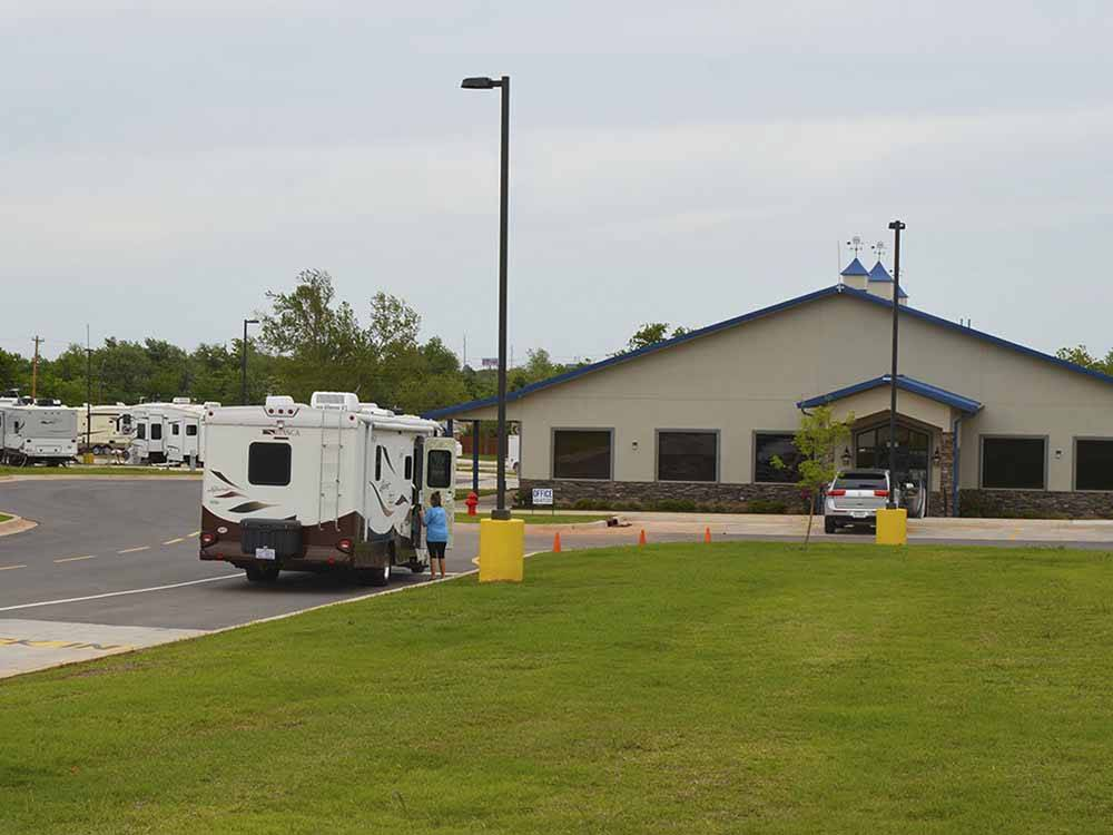 Large community building with bright blue roof at ROADRUNNER RV PARK
