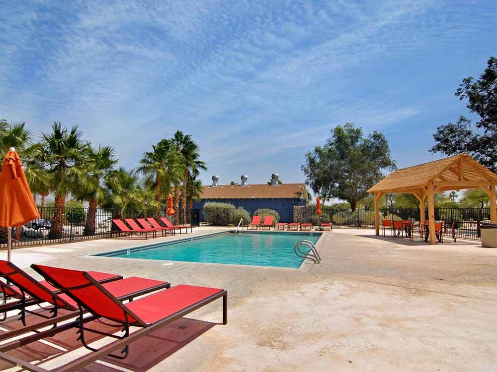 Swimming pool with outdoor seating at PALM CANYON HOTEL AND RV RESORT
